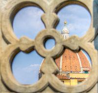 Duomo Santa Maria Del Fiore dome behind an ornate balcony in Florence, Tuscany, Italy