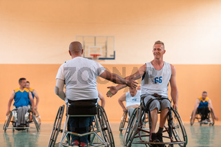 a team of war veterans in wheelchairs playing basketball, celebrating points won in a game. High five concept