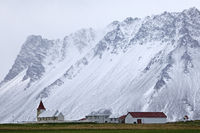 Small church with farm in front of snow-covered mountain, Stadastadur, Snæfellsnes, Iceland