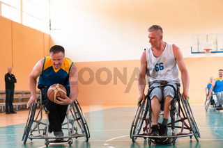 Disabled War or work veterans mixed race and age basketball teams in wheelchairs playing a training match in a sports gym hall. Handicapped people rehabilitation and inclusion concept