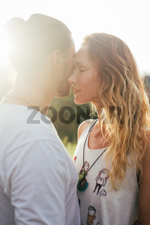 Young woman hugging asian man in the middle of a wheat field and kissing each other.