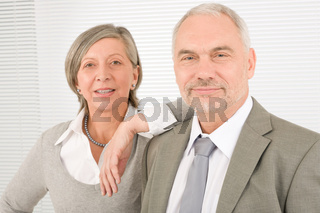 Senior businesspeople lean over shoulder colleague