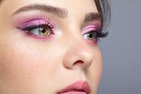 Closeup shot of human female face with pink makeup.