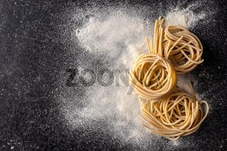 Italian pasta nest. Uncooked spaghetti nest and flour.