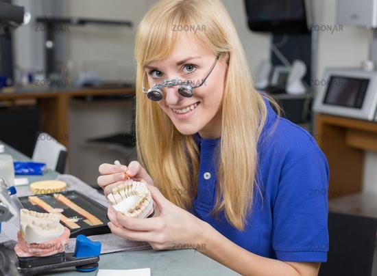 Dental lab technician applying porcelain to dentition mold