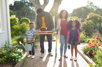 Happy african american family standing with garden tools and looking at camera