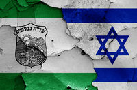 flags of Givatayim and Israel painted on cracked wall