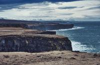 Stormy sea near rough cliffs in Iceland