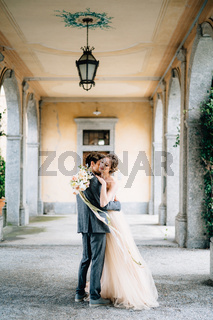 Groom hugs and kisses bride with a bouquet of flowers on an old terrace with columns entwined with green ivy. Lake Como