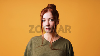 portrait of pretty young woman with red hair bun and curtain bangs
