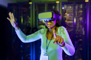 Happy african american female computer technician wearing vr headset and working in server room