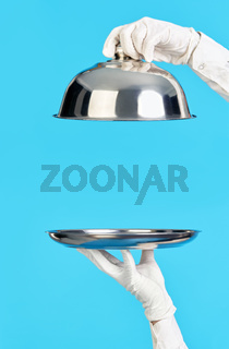Elegant waiter's hands in white gloves holding silver tray and cloche on blue background