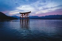 The floating Torii Gate of Itsukushima Shrine in ocean waves after sunset, Miyajima, Japan