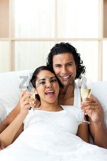 Happy young lovers drinking Champagne