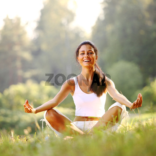 yoga woman on green grass in lotus pose