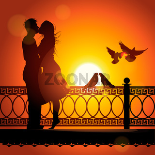 Silhouette of couple in love kissing at sunset