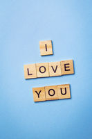 The inscription on wooden cubes I love you, laid out on a blue background, top view.