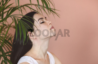 Young brunette near green plant