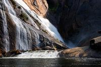 Ezaro waterfall water crashing on lake between rocks in Spain