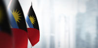 Small flags of Antigua and Barbuda on a blurry background of the city