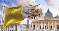 The flag of the Vatican city state fluttering in the wind with St. Peter's basilica