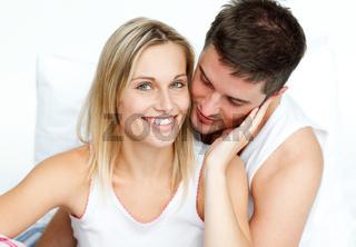 Man hugging his girlfriend in bed