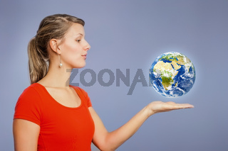 woman watching planet earth above her hand