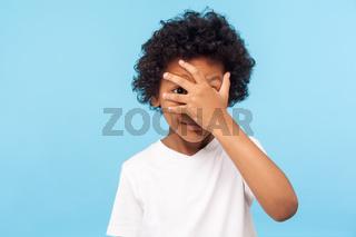 Portrait of emotional curly boy on blue background.