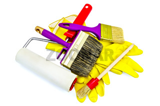 Brushes of various sizes with yellow gloves and roller