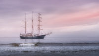 Rolling wave in front of tall ship covered in haze, anchored near Northern Ireland coast