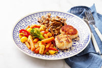Plate with fried vegetables, carrots, broccoli, baby corn, bell peppers, roasted champignons and two chicken balls