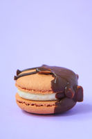 chocolate Cake macaron or macaroon on purple background.