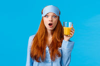 Amazed and speechless caucasian foxy woman in nightwear, pyjama and sleep mask, open mouth wondered, stare camera as holding orange juice, watching news morning breakfast, blue background