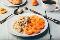 Porridge with apricot, coffee, glass of juice and croissant