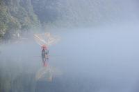 casting fishing net closeup on mist river
