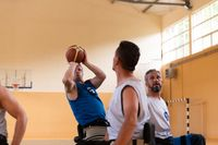 handicapped war veterans in wheelchairs with professional equipment play basketball match in the hall.the concept of sports with disabilities