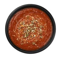 Bowl of tomato soup in black bowl, top view