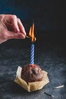 Hand lighting candle on birthday muffin