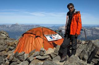 Junger Mann aus Nepal als Bergwächter am Informationsstand auf etwa 3100 Metern Höhe für Besteiger des Mont Blanc auf der klassischen Route über die Gouter Hütte nahe der Hütte Tête-Rousse