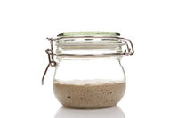 Active sourdough starter in a glass jar for homemade bread.