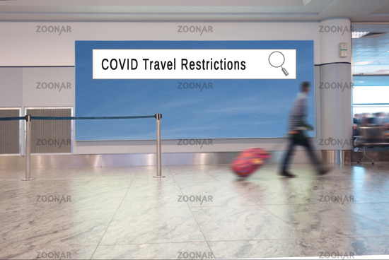 A man with suitcase walks in an airport, with COVID Travel Restrictions internet search window