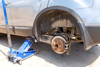 Сar at the tire mounting with removed wheel on pneumatic jack