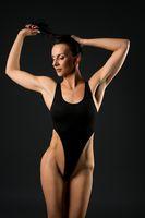 Fit woman in sexy bodysuit in studio