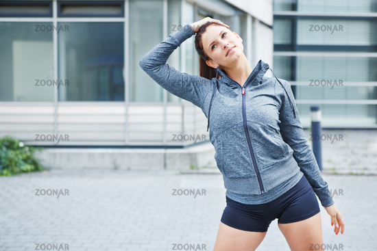 Junge Frau dehnt Muskeln vor dem Sport