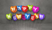 Colorful happy new year heart shape balloons on a grey concrete background. Horizontal banner