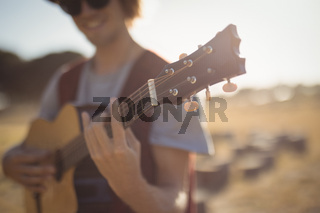Close up of young man playing guitar while standing on field