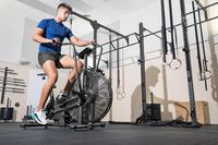 Fit man doing cardio training on stationary air bike machine with fan at the gym.