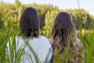 Two young women brunette and blonde are standing in a field.