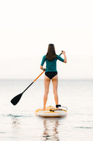 Young girl on a sup board with a paddle in her hand - shot from the back, calm surface of the sea - copy space