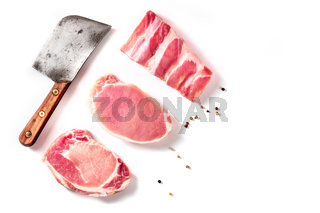 Raw pork meat, different cuts, shot from above on a white background